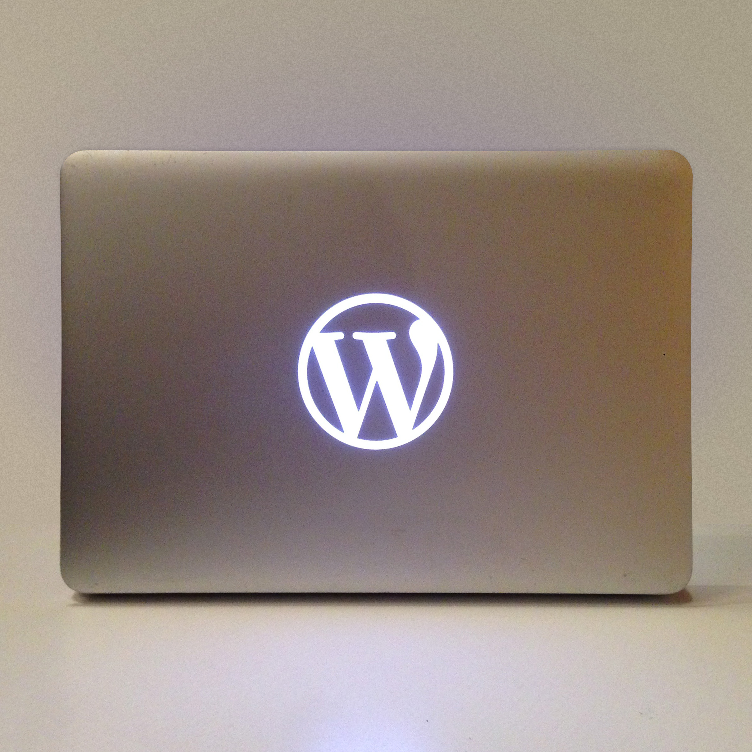 Photo of a customized Macbook Pro, 2012 edition, with the WordPress logo